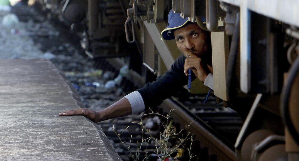 Um migrante do Oriente Médio se esconde debaixo do trem na Macedônia, 17 de agosto de 2015