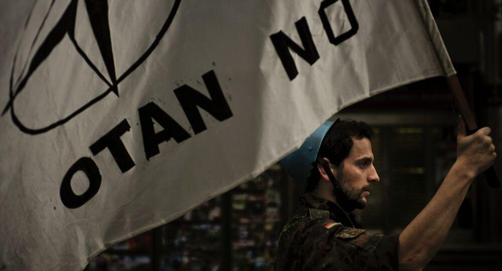 Um membro do movimento pacifista com a bandeira No OTAN