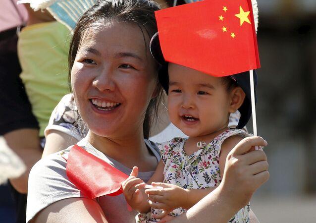 Uma mulher com o seu bebê está a espera da exibição de helicópteros e aviões durante a parada militar em homenagem aos 70 anos da vitória na Segunda Guerra Mundial, Pequim, China, 3 de setembro de 2015
