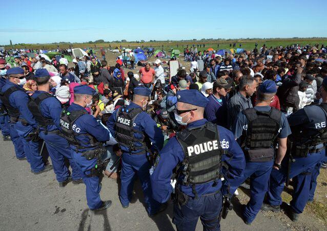 Migrantes e policiais perto da fronteira entre a Hungria e Sérvia, aldeia  Roszke, 7 de setembro de 2015