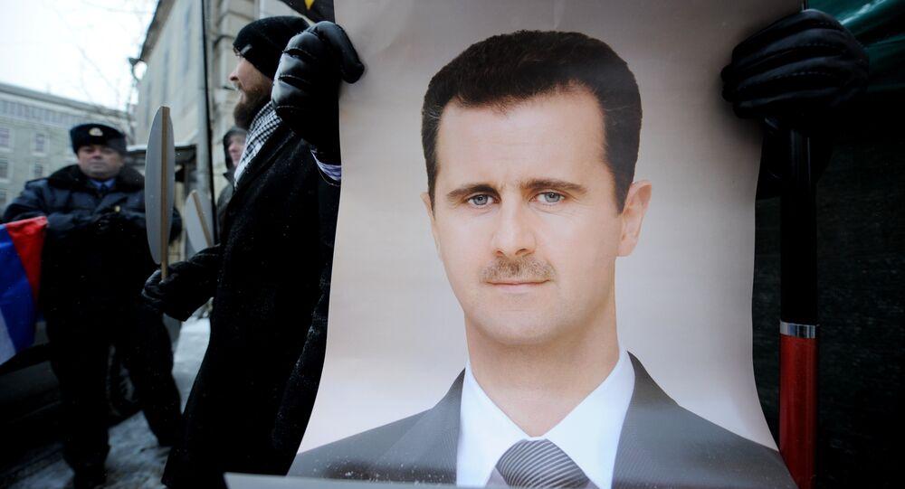 Manifestante exibe cartaz com imagem do presidente sírio, Bashar Assad, durante uma ação de apoio perto da Embaixada da Síria em Moscou (arquivo)