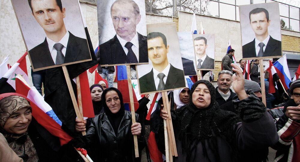 Sírios com as fotos do presidente sírio Bashar Assad e primeiro-ministro russo Vladimir Putin em Damasco