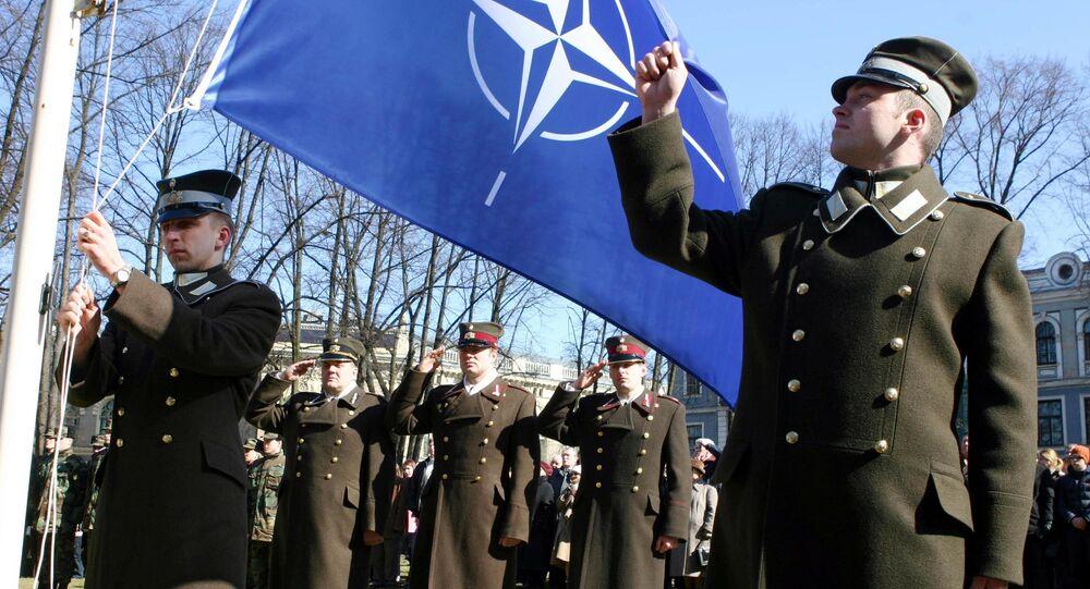 Funcionários da Letônia durante cerimônia de hasteamento da bandeira da OTAN em frente ao Castelo da Presidência em Riga