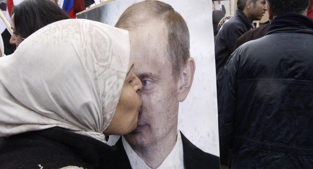 Mulher síria beija um poster do presidente russo Vladimir Putin durante uma manifestação pró-governo sírio em frente à embaixada russa em Damasco