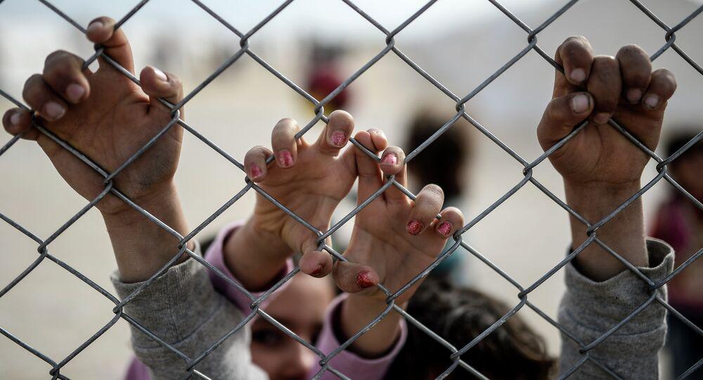 Mãos das crianças curdos sírios no campo de refugiados