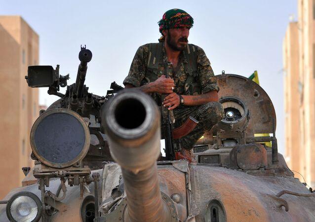 Combatente curdo senta em tanque do Exército sírio.
