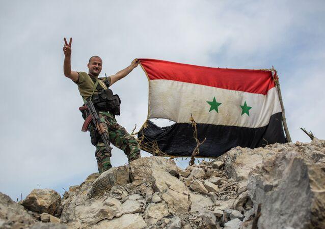 Soldado sírio com a bandeira do país em montanha perto de Kessab, na fronteira com a Turquia