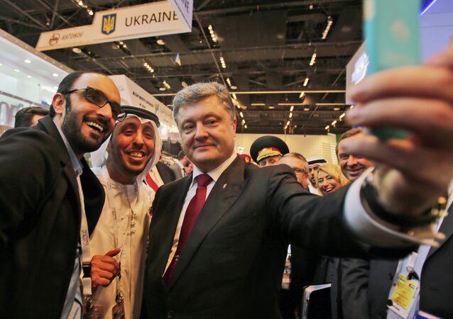 Ukrainian President Petro Poroshenko takes a selfie with an Emirati media representative at the International Defence Exhibition and Conference, IDEX, in Abu Dhabi, United Arab Emirates