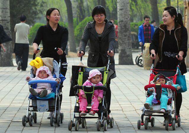 Mães chinesas levam seus filhos para passear.