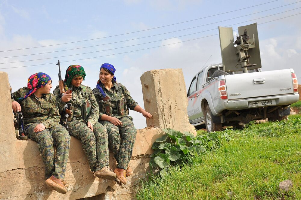 Milicianas curdas da Unidades de Proteção das Mulheres (YPJ) sentam-se ao lado de um carro com uma metralhadora pesada. Um campo de treinamento em al-Qahtaniyah, perto da fronteira sírio-turca.