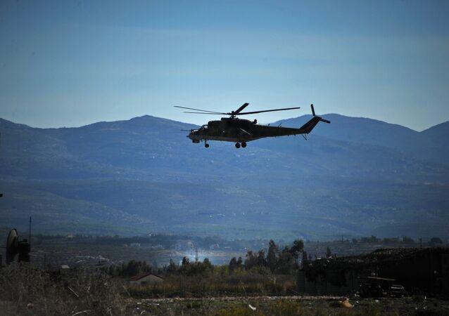 Um helicóptero Mi-24 russo patrulha a base aérea russa Hmeymim na Síria (foto de arquivo)