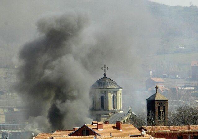 Uma coluna de fumaça sobre a Igreja Ortodoxa da Sérvia, que foi incendiada pelos extremistas da etnia albanesa em Kosovska Mitrovica, no norte de Kosovo, quinta-feira, 18 de março, 2004