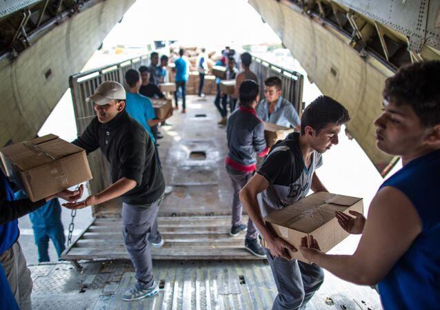 Pessoas descarregando avião russo EMERCOM com ajuda humanitária que chegou ao aeroporto de Latakis na Síria