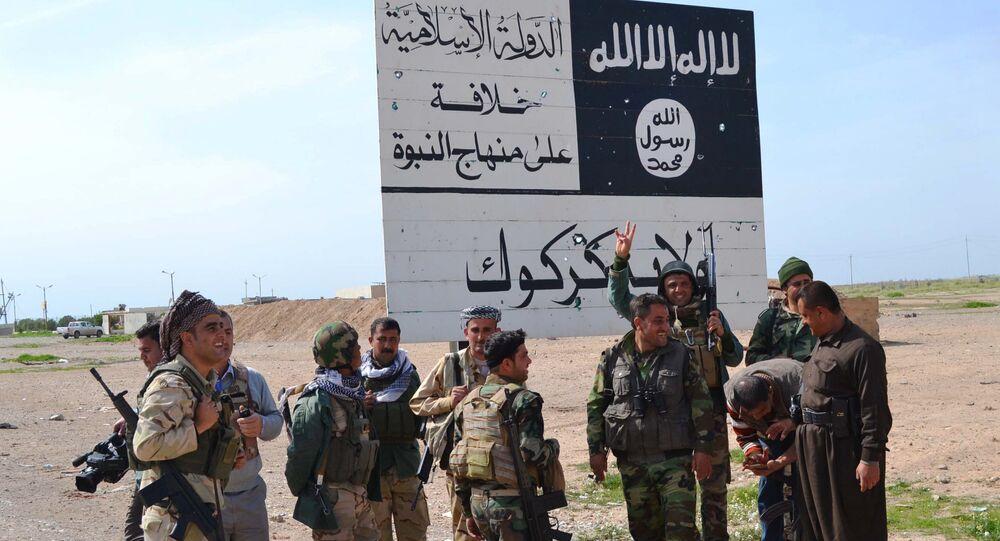 Combatentes peshmerga do Curdistão iraquiano ao lado de uma placa do Daesh (Estado Islâmico)