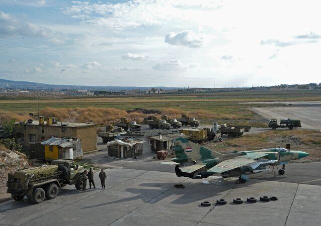 A base aérea de Hama. Carros russos e o caça MiG-23 russo das Forças Aéreas da Síria