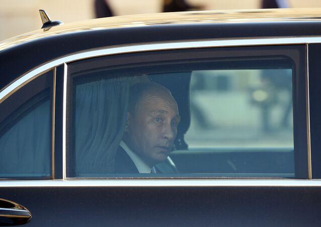 Vladimir Putin olha pela janela do carro presidencial