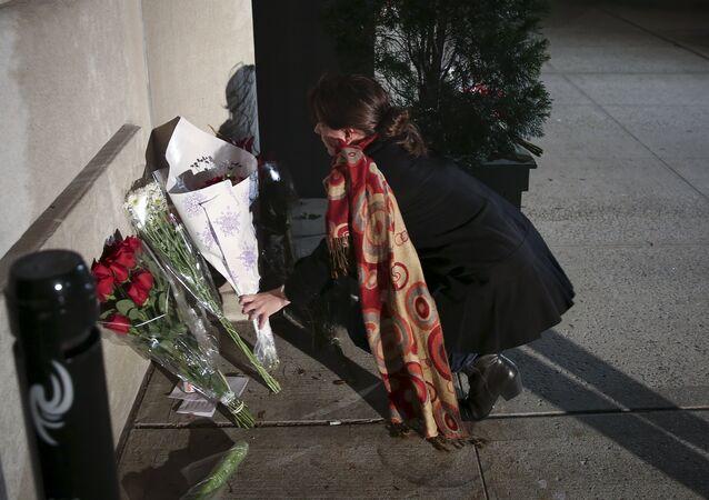 Uma mulher deposita flores na entrada do consulado da França em Nova York, depois de ouvir notícia dos atentados (foto de arquivo)