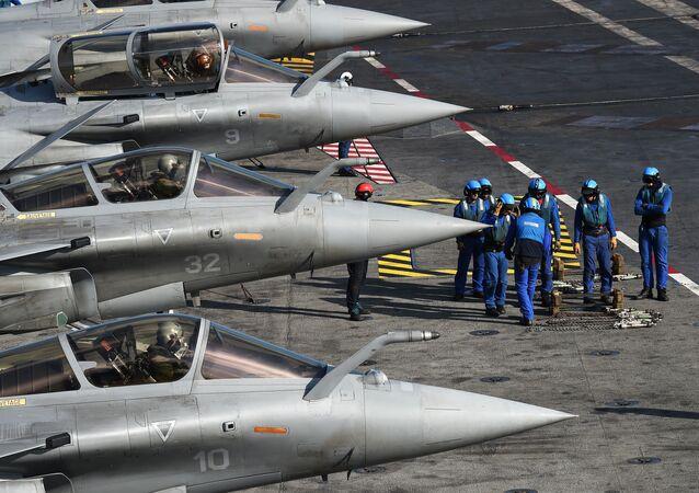Militares franceses ao lado de caças Rafale no convés do porta-aviões Charles de Gaulle no Mar Mediterrâneo
