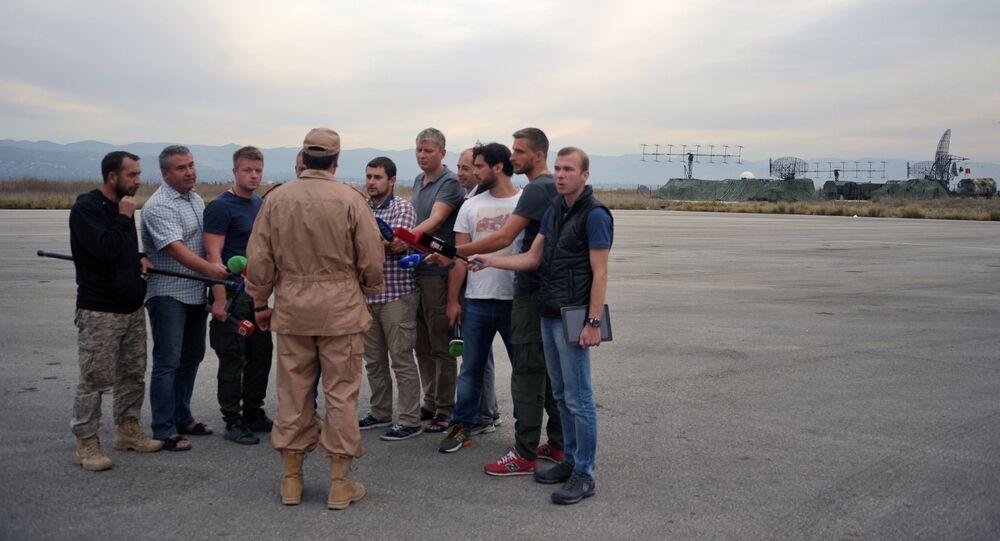 Piloto salvo do Su-24, Konstantin Murakhtin, (ao centro de costas) fala com jornalistas na base áerea de Hmeymim, Lataquia, Síria, 25 de novembro de 2015