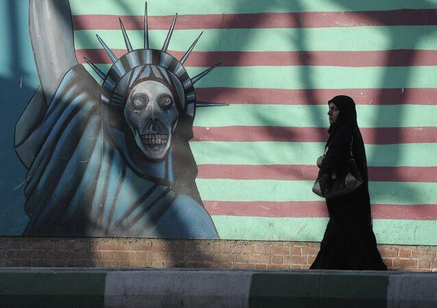 Mulher em frente ao muro da antiga embaixada dos EUA em Teerã, tomada por islâmicos em 1980
