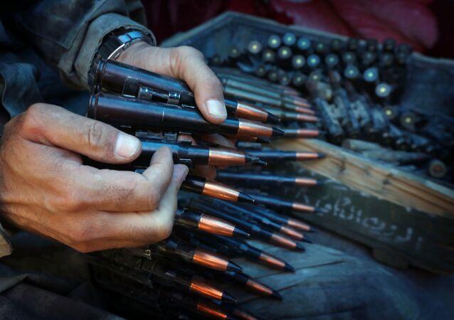 Um militante prepara um cinto de munição