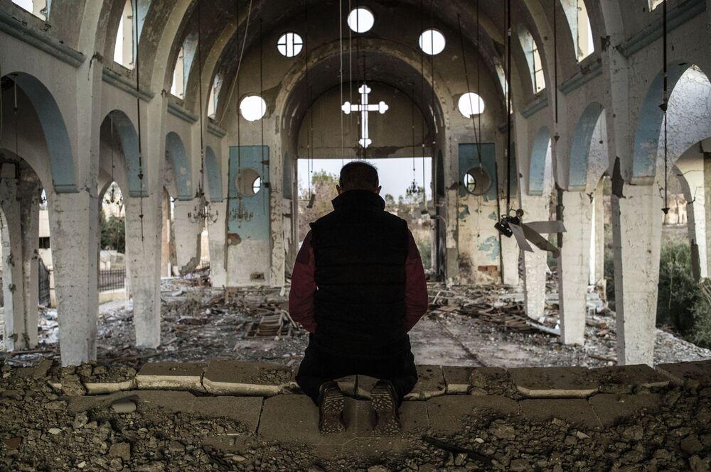 Morador de uma aldeia cristão da província de Al-Hasaka, no nordeste da Síria, reza na igreja de São Jorge destruída pelos terroristas do Daesh