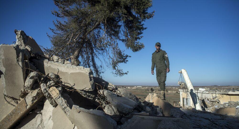 Soldado sírio analisa ruínas de uma aldeia cristã destruída pelo Daesh no nordeste da Síria
