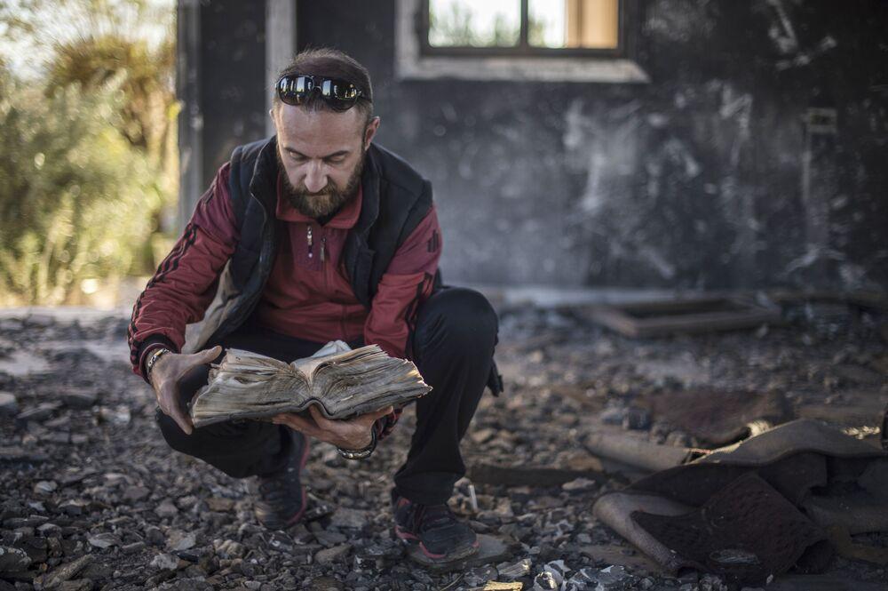 Morador encontra a Bíblia em ruínas de um vilarejo cristão destruído pelo Daesh na província de Al-Hasaka, nordeste da Síria
