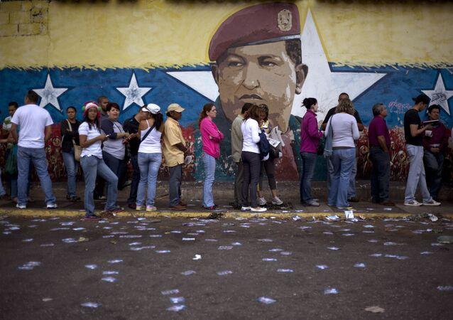 Venezuelanos em fila para participar de eleições em seu país tendo ao fundo imagem de Hugo Chávez pintada em muro