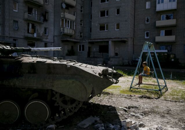 Uma criança junto ao edifício danificado, Donbass