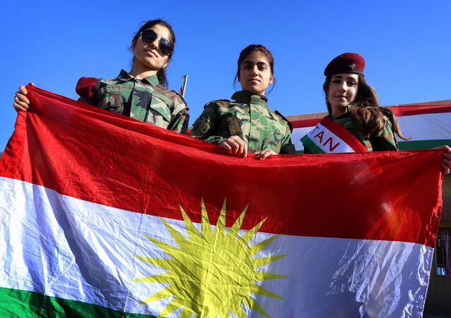 Moças curdas seguram a bandeira da Curdistão iraquiano na cidade de Arbil