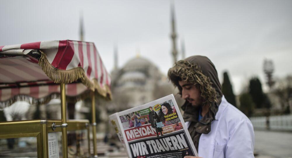 Homem empunha um jornal turco com o título em alemão Choramos perto de local do atentado em Istambul, Turquia, 13 de janeiro de 2016