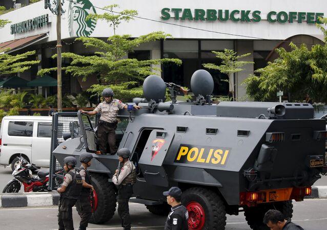 Policiais indonésios armados e um carro blindado no local de uma explosão ocorrida em Jacarta em 2016