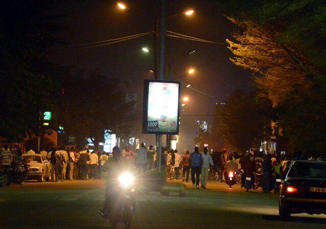 As pessoas se reúnem na avenida de Kwame Nkrumah perto de Hotel Splendid onde os atacantes permanecem na capital do Burkina Faso de Ouagadougou em 15 janeiro de 2016.