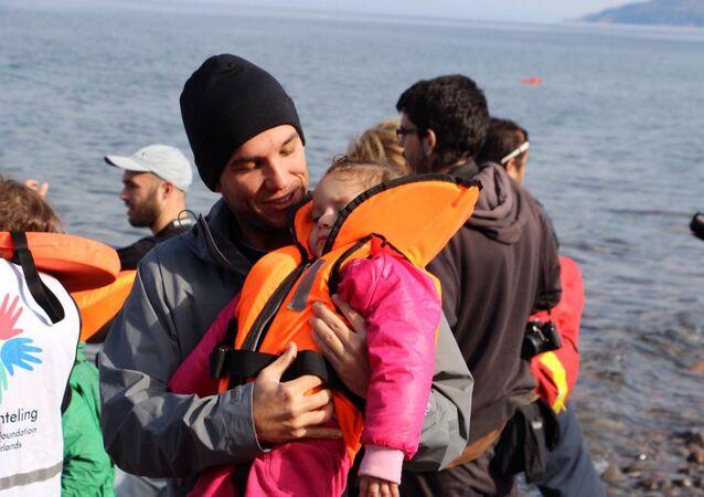 Edgard Raoul com criança refugiada desfalecida, na Ilha de Lesbos, na Grécia.