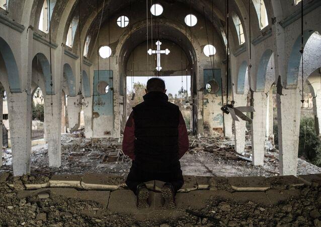 Cristão de vilarejo no nordeste da Síria reza em igreja destruída pelo Estado Islâmico