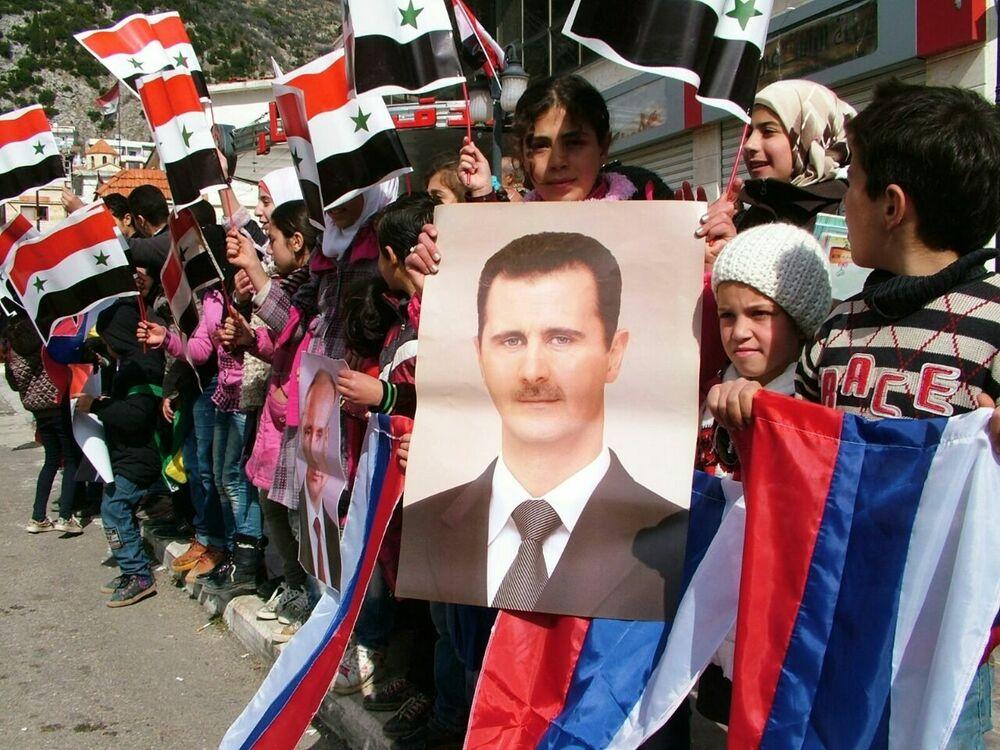 Aguardando a distribuição da ajuda humanitária russa, jovens fazem fila e mostram cartazes com retratos dos presidentes sírio e russo e bandeiras desses países