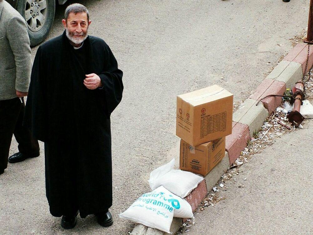 Um homem olha o fotógrafo da Sputnik perto de uma caixa da ajuda humanitária russa, que chegou à cidade de Kessab, na Síria, em 12 de fevereiro