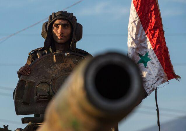 Soldados sírios sobre um veículo autopropulsado de artilharia