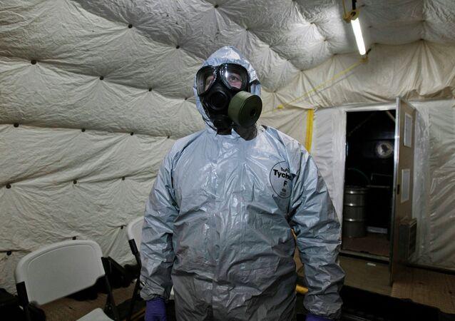 Especialista mostra a jornalistas as roupas especiais utilizadas durante a neutralização de armas químicas