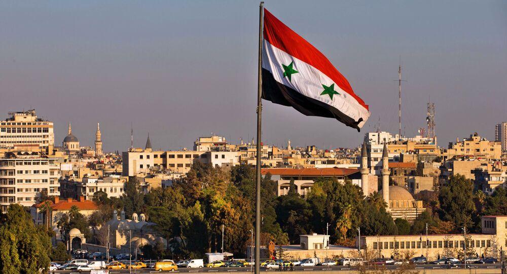 Bandeira síria esvoaçando enquanto os carros seguem por ponte durante a hora de ponta, Damasco, Síria, 28 de fevereiro de 2016