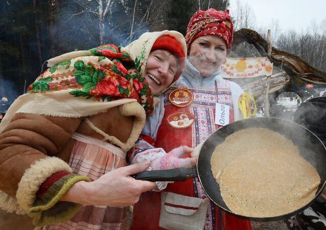 Mulheres cozinham blinis nas comemorações da Maslenitsa em Moscou