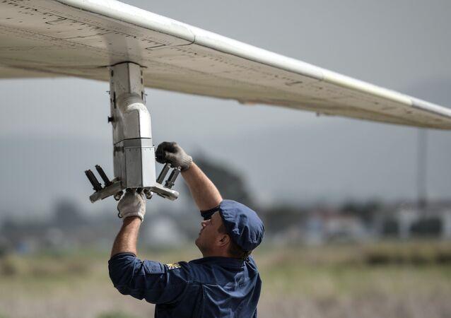 Um técnico fazendo manutenção de um Su-34 na base aérea de Hmeymim, na Síria