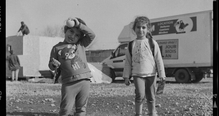 Pequenas refugiadas durante um jogo no campo de refugiados Linière, Grande-Synthe, França