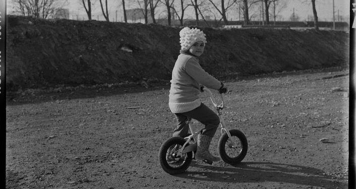 Pequena refugiada vai de bicicleta no campo de refugiados Linière, Grande-Synthe, França
