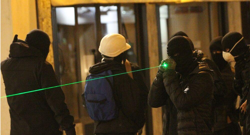 Um manifestante em máscara aponta algo com laser. Foto de arquivo (14 de fevereiro, 2016)