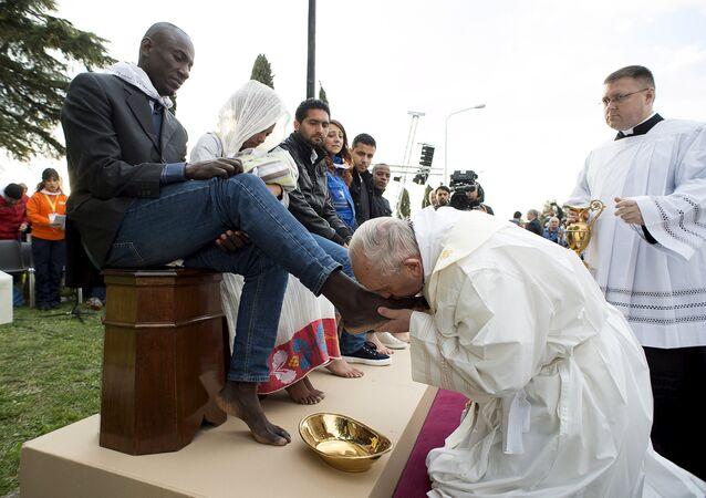 Papa Francisco beija os pés de um refugiado em cerimônia em Roma, Itália