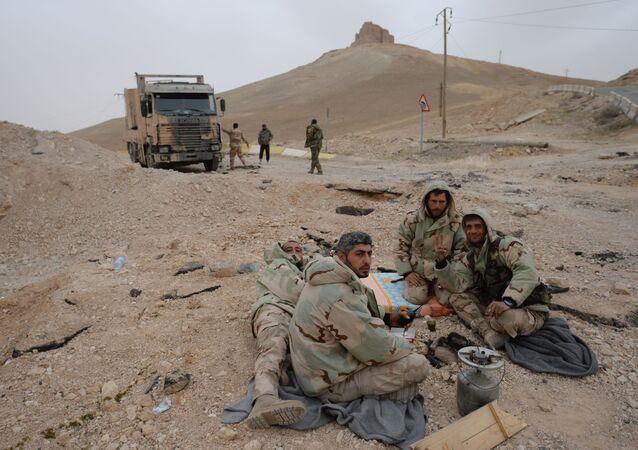 Soldados sírios descansam em uma pausa entre os combates na entrada de Palmira