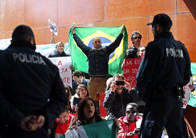 Polícia olha para um manifestante que se cobre com uma bandeira do Brasil e outros que mostram cartazes pró-democracia durante a conferência na Universidade de Lisboa em 31 de março