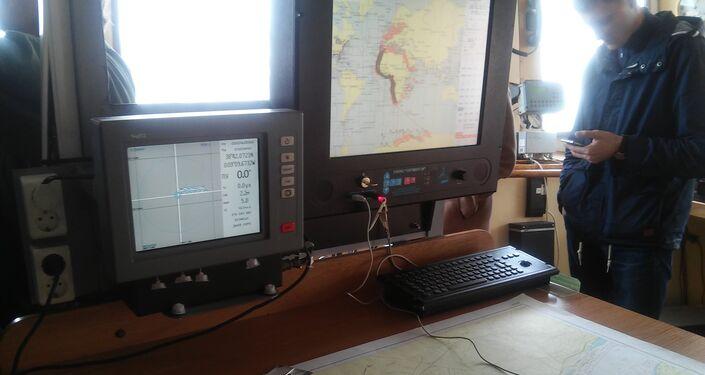 Uma pessoa convidada para ver o navio Admirla Vladimirsky, em 4 de abril de 2016, em Lisboa, está junto a equipamento e mapa interativo